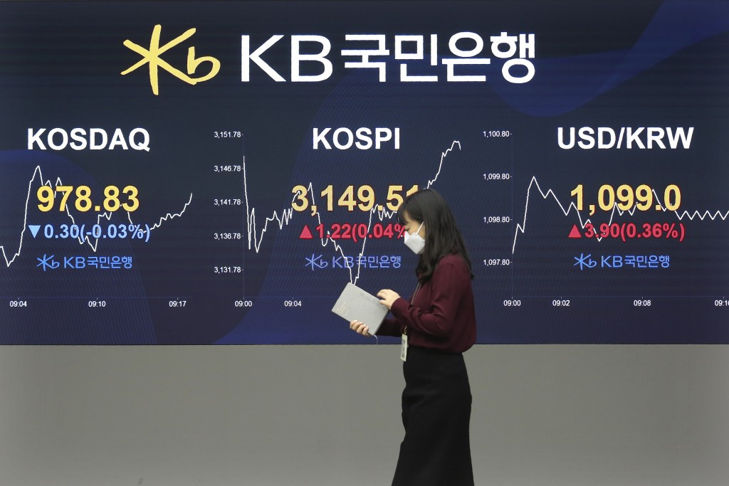 A currency trader passes by monitors showing the Korea Composite Stock Price Inde, and foreign exchange rate at the foreign exchange dealing room of a...