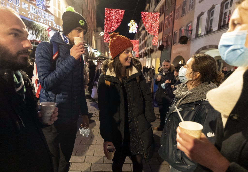 FILE - In this Dec. 17, 2020 file photo, people enjoy a glass of mulled wine in the street before the curfew in Strasbourg, eastern France. Trying to ...