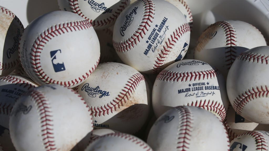FILE - In this Feb. 14, 2020, file photo, baseballs occupy a bucket after use during fielding practice during spring training baseball workouts for pi...