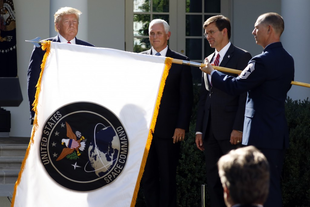 FILE _ In this Aug. 29, 2019 file photo, President Donald Trump watches with Vice President Mike Pence and Defense Secretary Mark Esper as the flag fo...