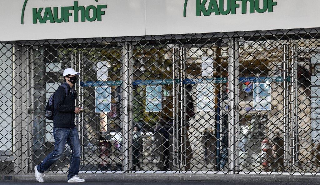 FILE - In this Monday, April 20, 2020 file photo, a man with a face mask to protect against the coronavirus walks past a Galeria Kaufhof warehouse as ...
