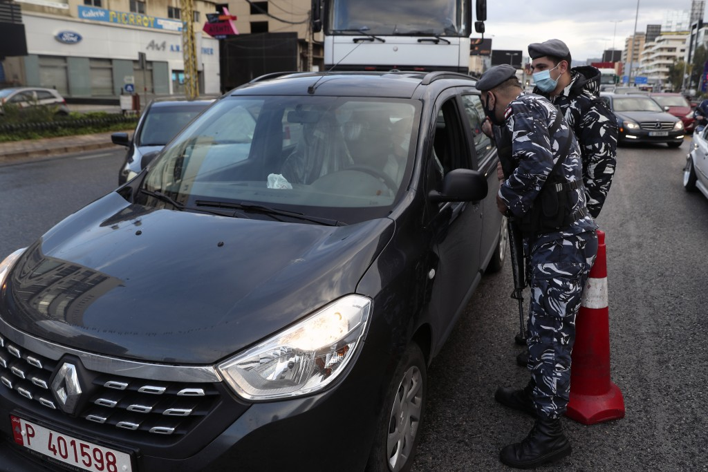 Police officers stand at a checkpoint to inspect cars that violate the lockdown, in Beirut, Lebanon, Thursday, Jan. 14, 2021. Lebanese authorities beg...