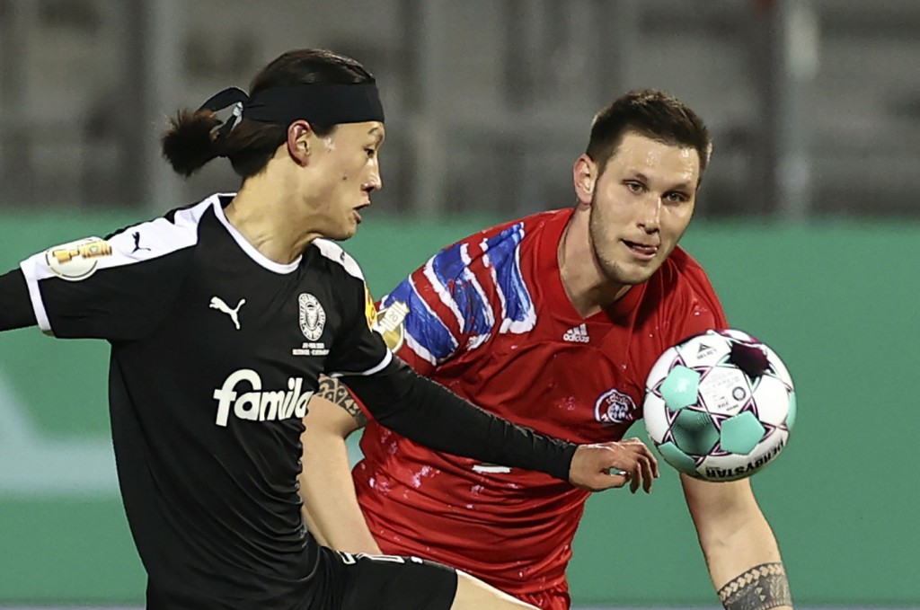 Kiel's Jae-sung Lee and Munich's Niklas Sule, right, in action during the DFB Cup 2nd round match between Holstein Kiel and Bayern Munich at the Holst...