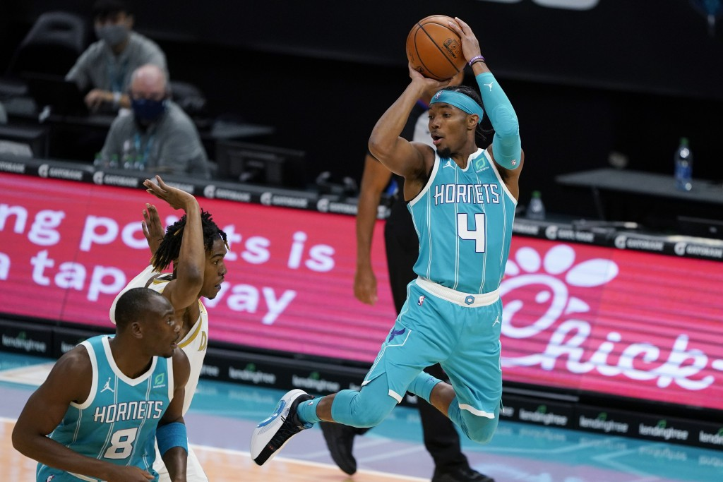 Charlotte Hornets guard Devonte' Graham looks to pass the ball during the first half of the team's NBA basketball game against the Dallas Mavericks in...