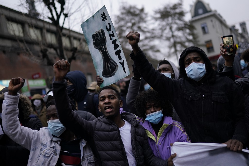 People shout slogans in the Belgium capital, Brussels, Wednesday, Jan. 13, 2021, during a protest asking for authorities to shed light on the circumst...
