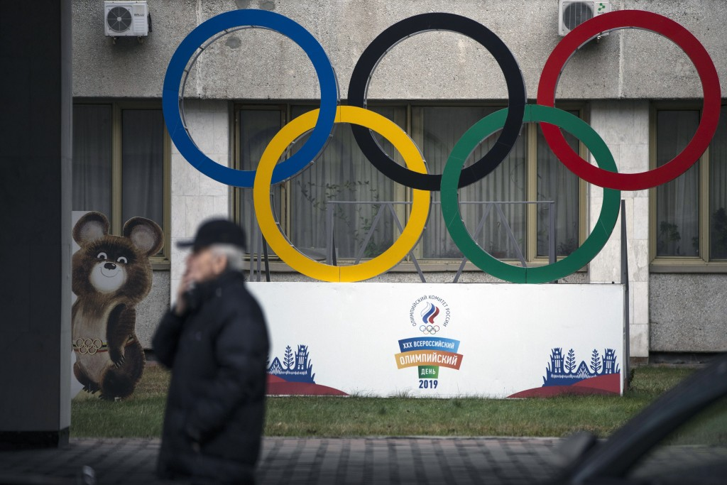 FILE - In this Nov. 28, 2019 file photo Olympic Rings and a model of Misha the Bear Cub, the mascot of the Moscow 1980 Olympic Games, left, are seen i...