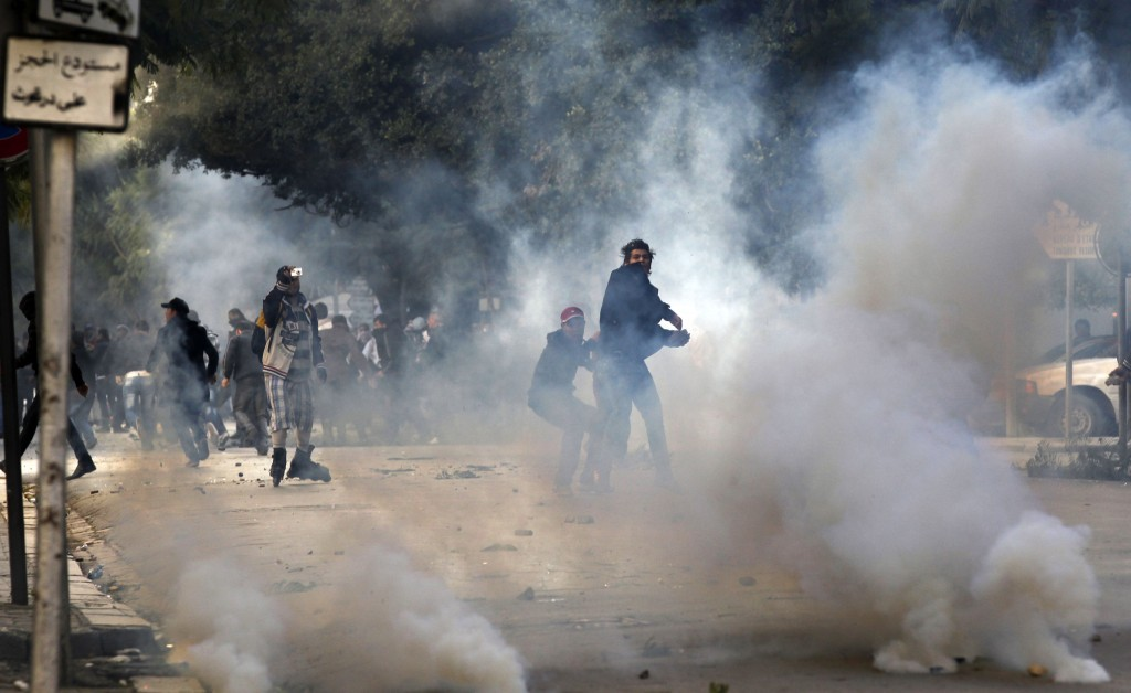 FILE - In this file photo dated Friday, Jan. 14, 2011, a demonstrators throws a stone at police during clashes in Tunis. Tunisia's president declared ...