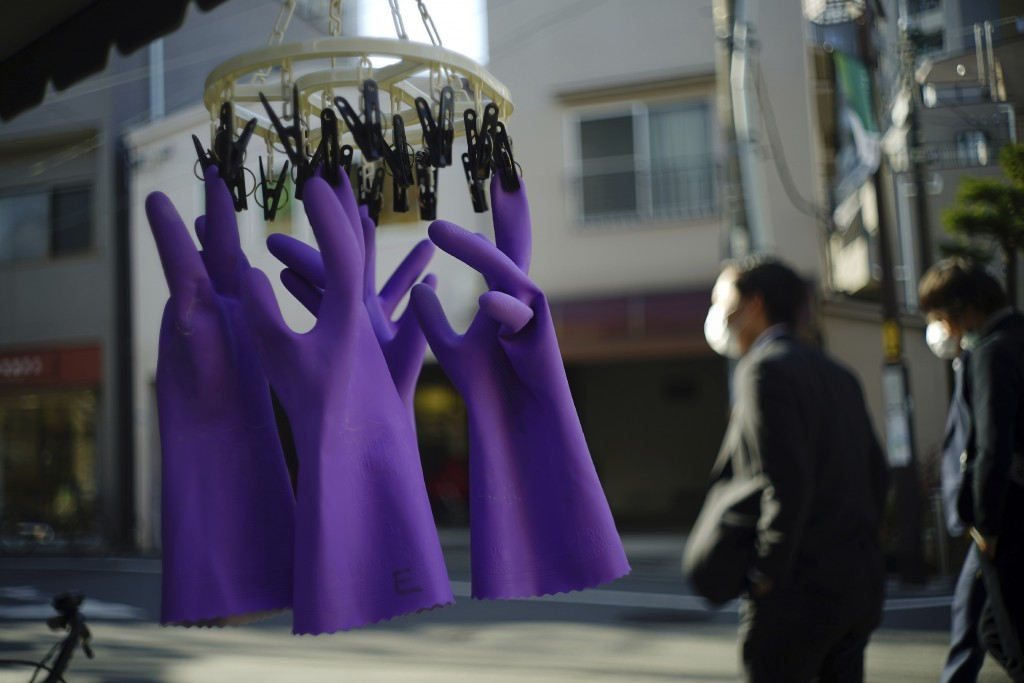 Rubber gloves hang to dry as people wearing protective masks to help curb the spread of the coronavirus walk past in Tokyo Thursday, Jan. 14, 2021. Th...