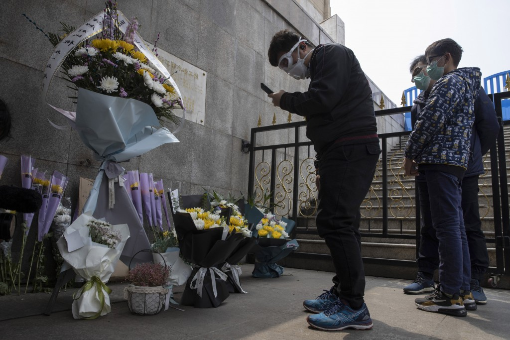 FILE - In this April 4, 2020, file photo, residents wearing masks stand in front of flowers placed near the Heroes Memorial Monument after a national ...
