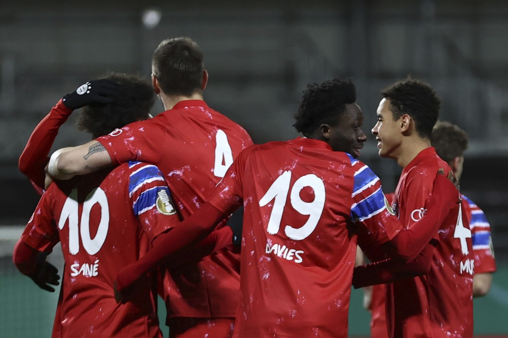 Munich's Leroy Sane, left, celebrates scoring with teammates during the DFB Cup 2nd round match between Holstein Kiel and Bayern Munich at the Holstei...