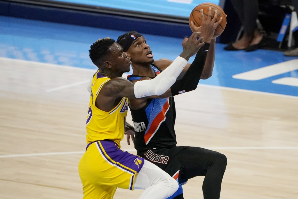 Oklahoma City Thunder guard Shai Gilgeous-Alexander, right, goes to the basket while defended by Los Angeles Lakers guard Dennis Schroeder during the ...