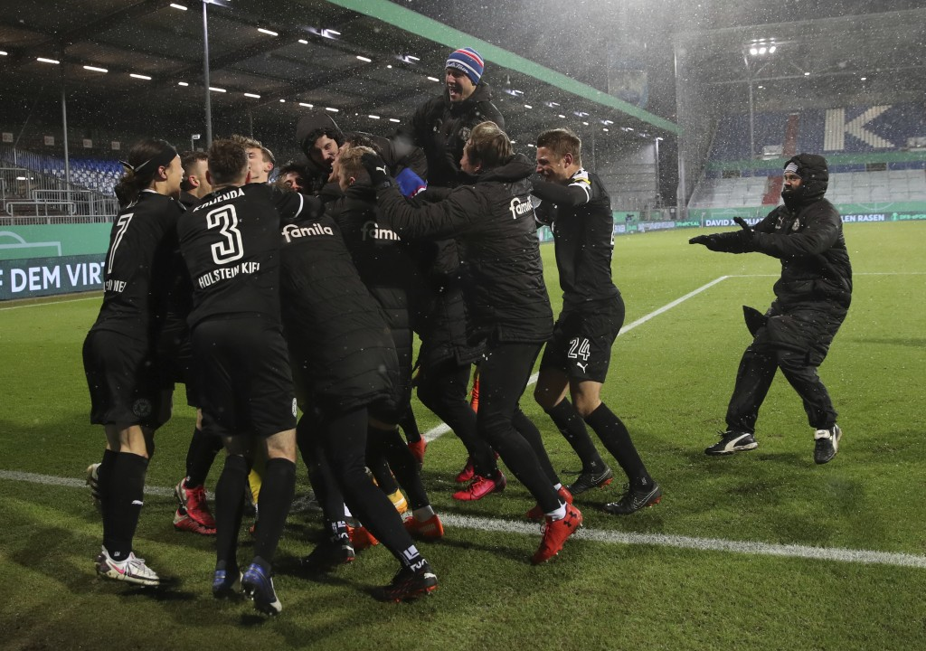 Kiel's players celebrate after beating Bayern Munich during the DFB Cup 2nd round match between Holstein Kiel and Bayern Munich at the Holstein Stadiu...