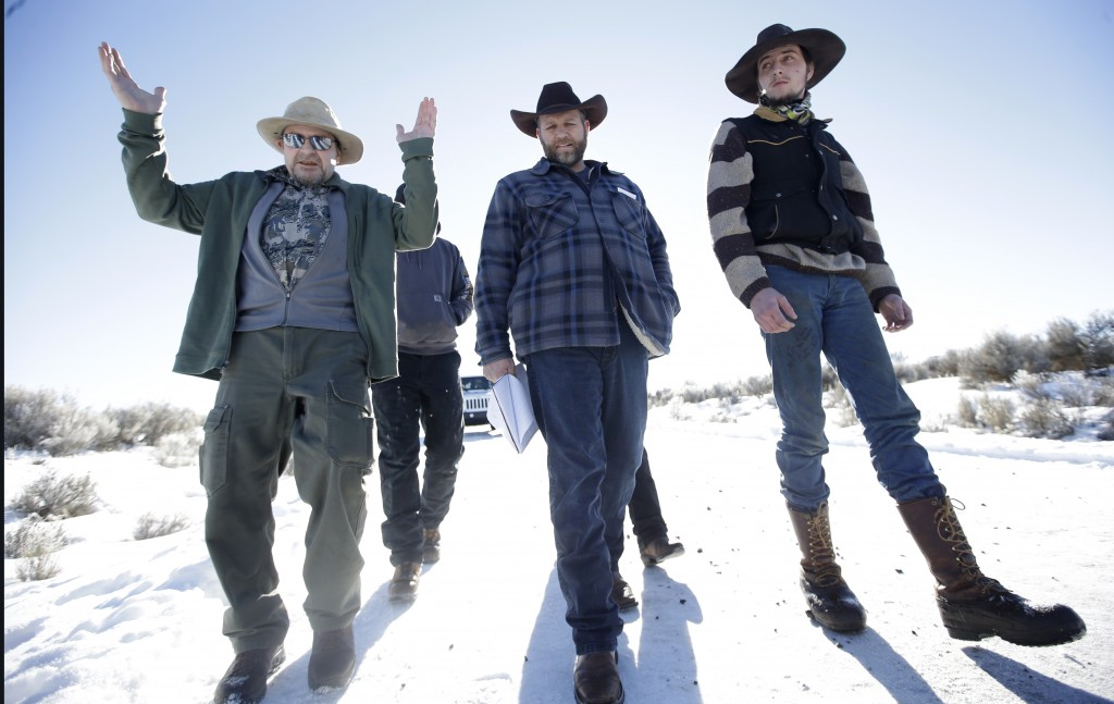 FILE - In this Jan 8, 2016, file photo, Burns resident Steve Atkins, left, talks with Ammon Bundy, center, one of the sons of Nevada rancher Cliven Bu...