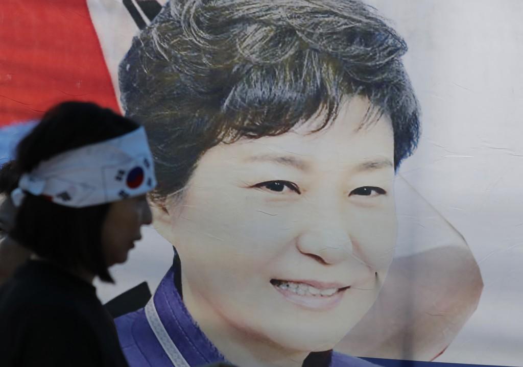 FILE - In this Aug. 29, 2019, file photo, a supporter of former South Korean President Park Geun-hye walks by the banner with her picture near the Sup...