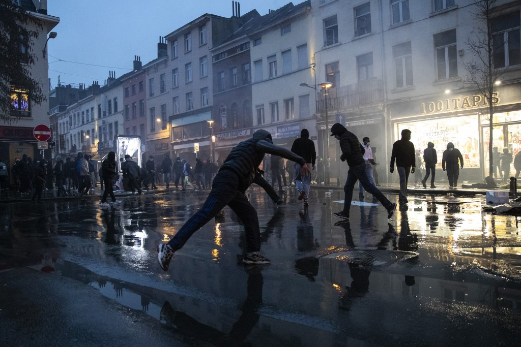 Protestors thrown stones in the Belgium capital, Brussels, Wednesday, Jan. 13, 2021, at the end of a protest asking for authorities to shed light on t...