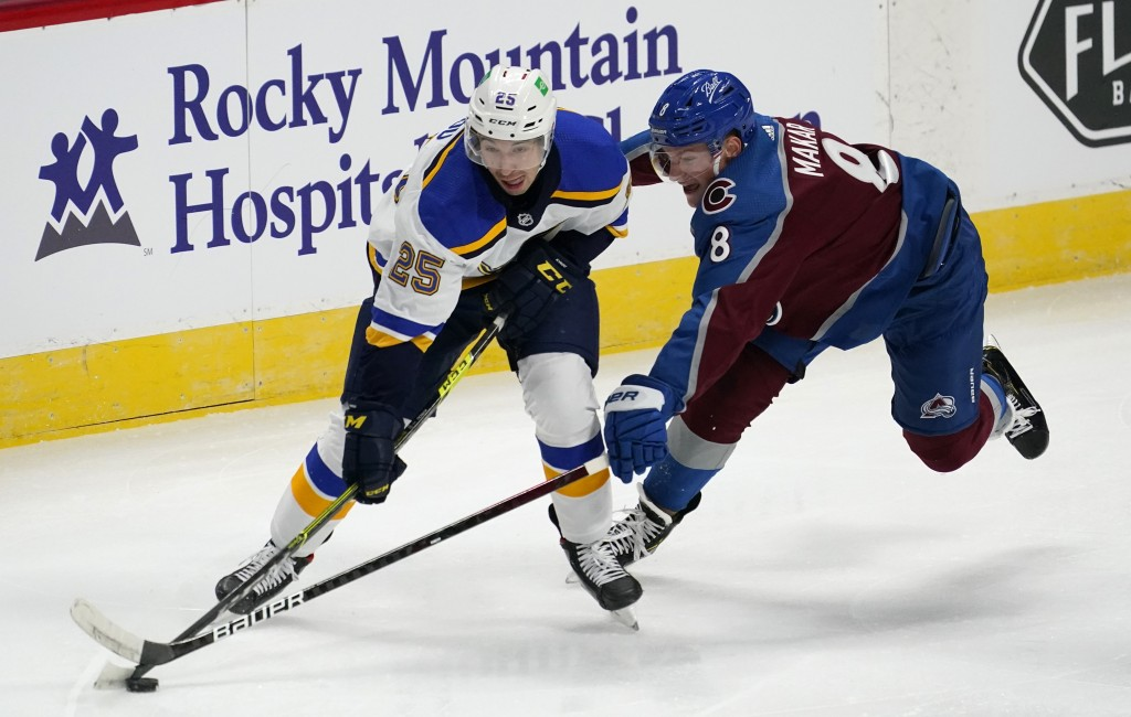 St. Louis Blues center Jordan Kyrou, left, looks to pass the puck as Colorado Avalanche defenseman Cale Makar reaches for it during the first period o...