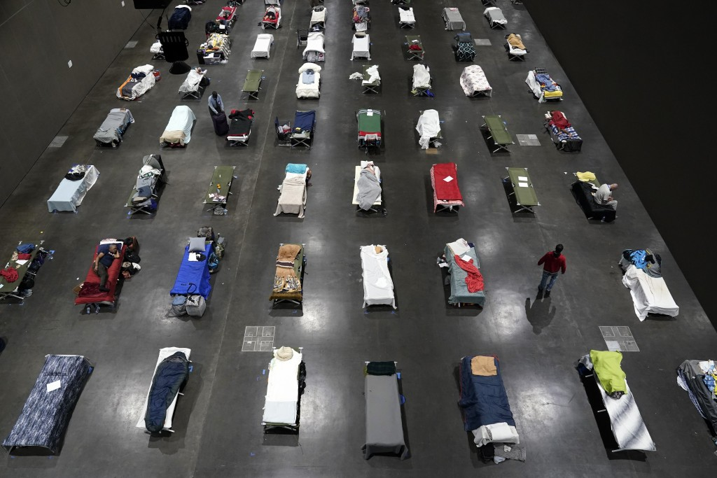 FILE - In this Aug. 11, 2020, file photo, beds fill a homeless shelter inside the San Diego Convention Center in San Diego. A coalition in California ...