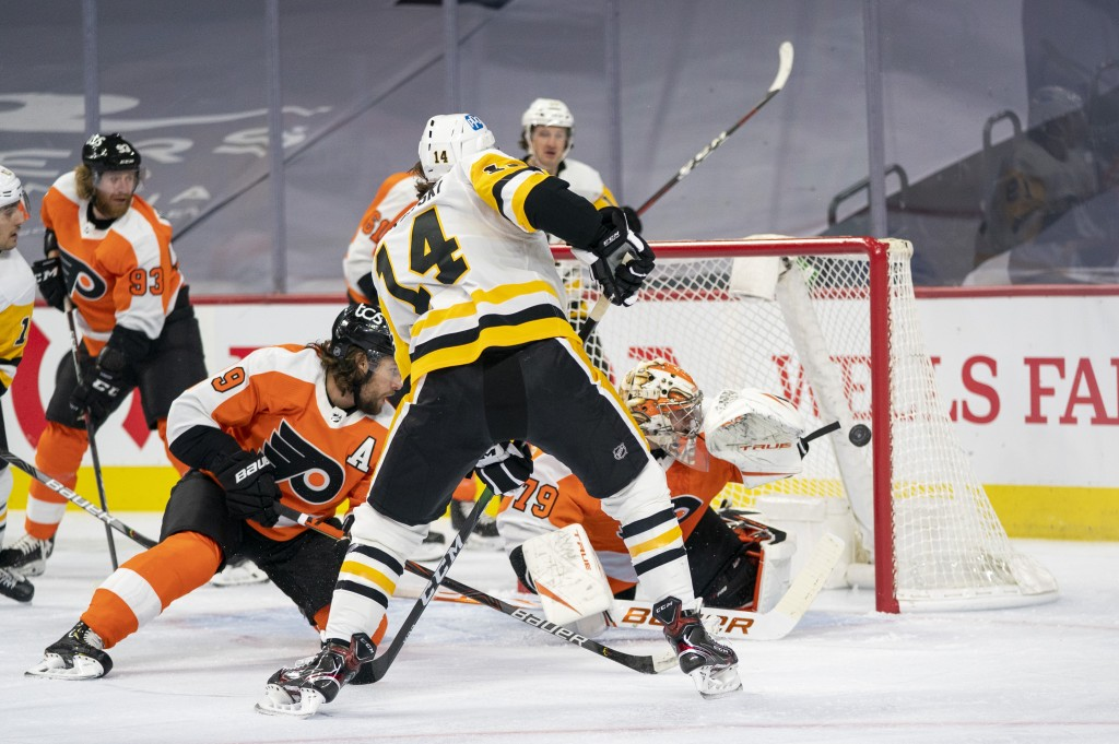 Pittsburgh Penguins' Mark Jankowski, center, shoots the puck past Philadelphia Flyers' goaltender Carter Hart, right, for a goal during the first peri...