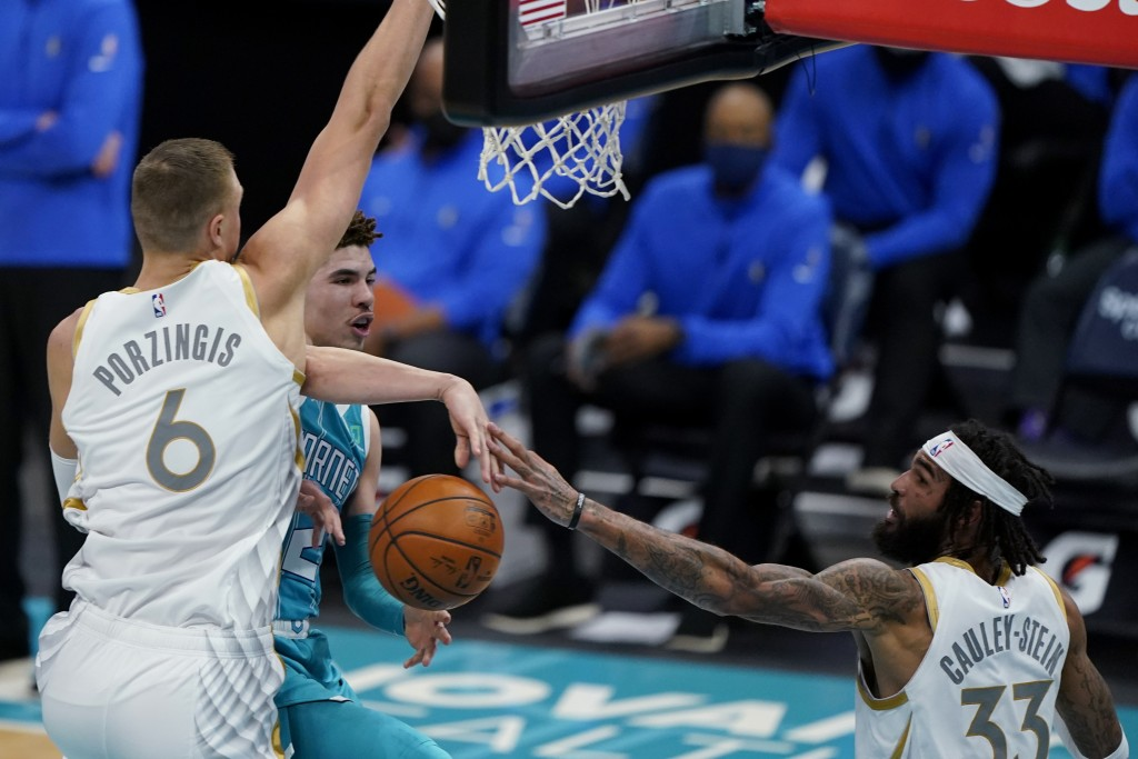 Charlotte Hornets guard LaMelo Ball passes the ball between Dallas Mavericks' Kristaps Porzingis, left, and Willie Cauley-Stein during the first half ...