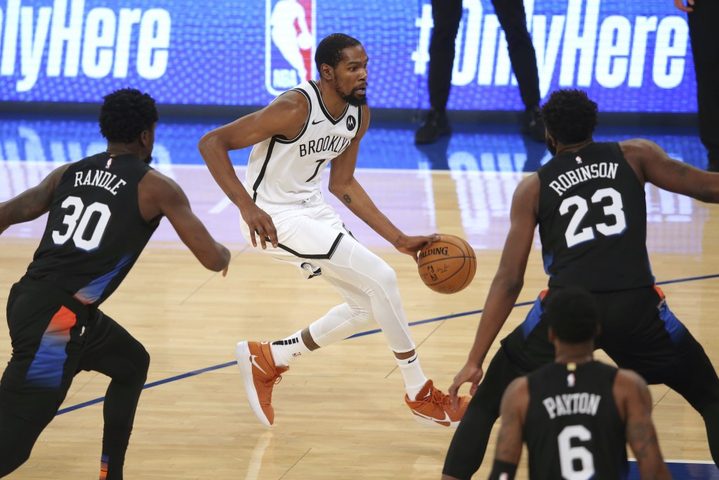 Brooklyn Nets forward Kevin Durant (7) dribbles the ball as New York Knicks forward Julius Randle (30) and center Mitchell Robinson (23) defend during...