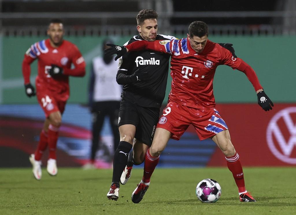 Kiel's Ahmet Arslan and Munich's Robert Lewandowski, right, in action during the DFB Cup 2nd round match between Holstein Kiel and Bayern Munich at th...