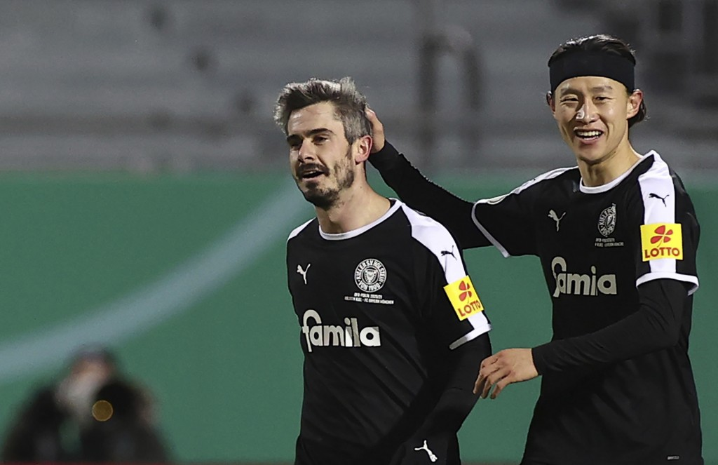 Kiel's Fin Bartels celebrates scoring with Jae-sung Lee, right, during the DFB Cup 2nd round match between Holstein Kiel and Bayern Munich at the Hols...
