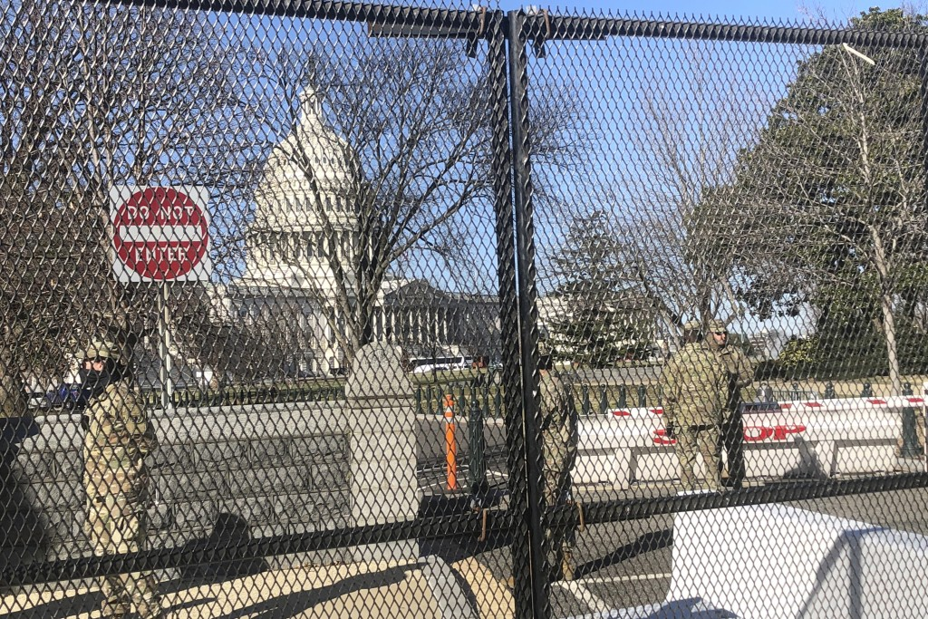 Members of the National Guard stand inside anti-scaling fencing that surrounds the Capitol, Sunday, Jan. 10, 2021, in Washington. Last week's mob atta...