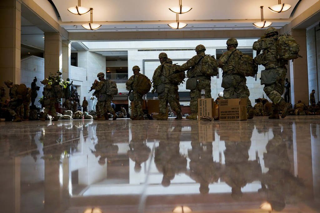 Troops move inside the Capitol Visitor's Center to reinforce security at the Capitol in Washington, Wednesday, Jan. 13, 2021. The House of Representat...