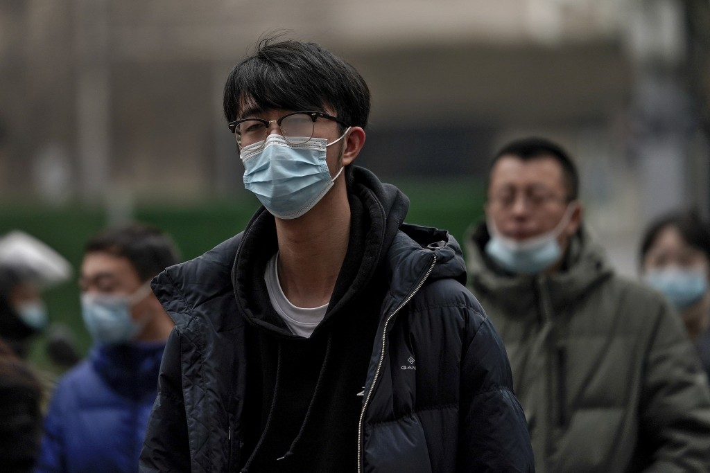 People wearing face masks to help curb the spread of the coronavirus walk across a street during the lunch break in Beijing, Thursday, Jan. 14, 2021. ...