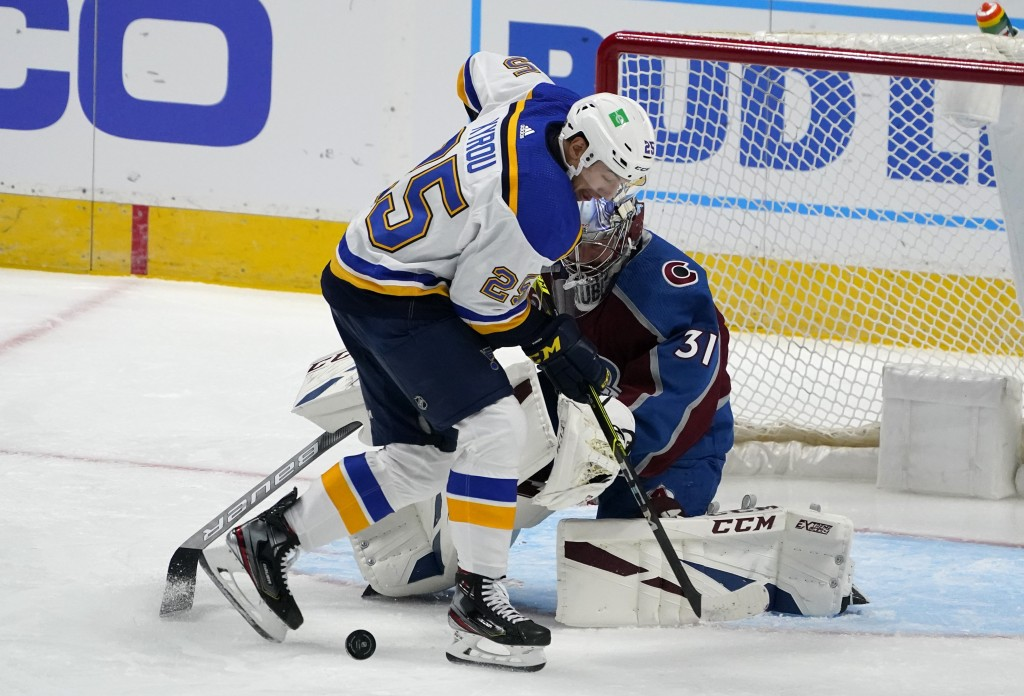 St. Louis Blues center Jordan Kyrou, front, struggles to direct a shot on Colorado Avalanche goaltender Philipp Grubauer during the first period of an...