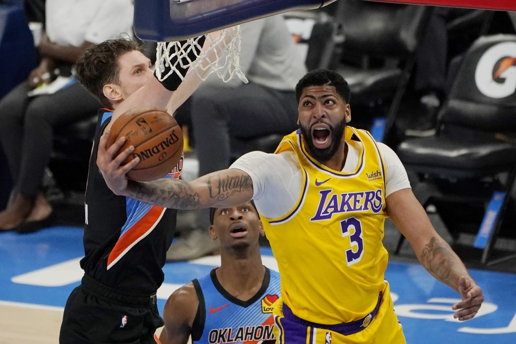 Los Angeles Lakers forward Anthony Davis (3) goes to the basket in front of Oklahoma City Thunder center Mike Muscala, left, and guard Shai Gilgeous-A...