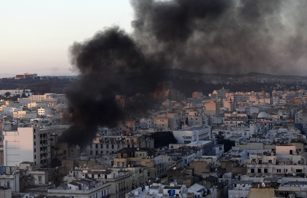 FILE - In this file photo dated Friday, Jan. 14, 2011, a column of smoke rises from buildings during clashes between protesters and police in Tunis. T...
