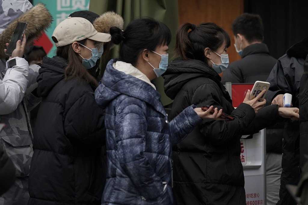 People wearing face masks to help curb the spread of the coronavirus show their health code and get temperature check before entering a shopping mall ...
