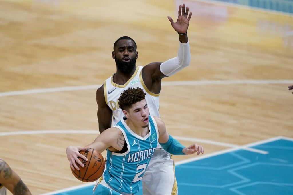 Charlotte Hornets guard LaMelo Ball drives around Dallas Mavericks forward Tim Hardaway Jr. during the first half of an NBA basketball game in Charlot...
