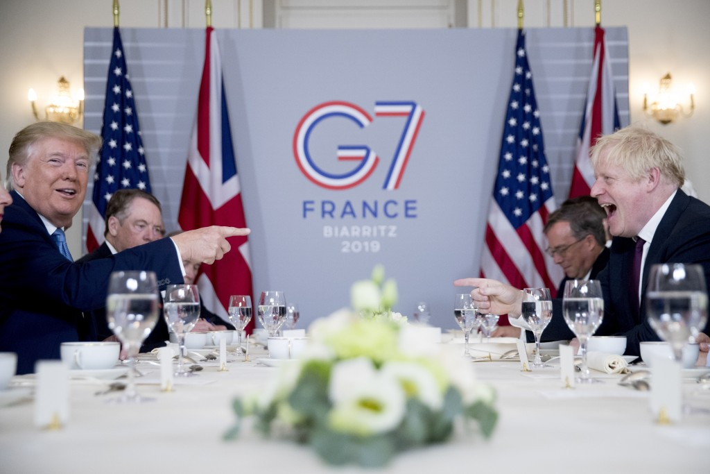 FILE - In this Aug. 25, 2019 file photo U.S. President Donald Trump, left, and Britain's Prime Minister Boris Johnson attend a working breakfast at th...