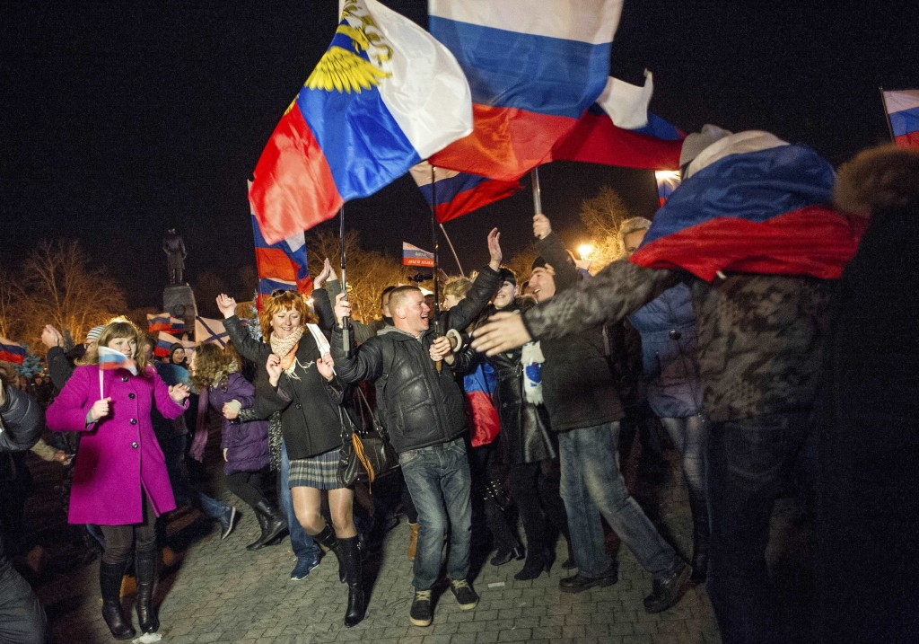 FILE - In this Sunday, March 16, 2014 file photo pro-Russian people celebrate in the central square in Sevastopol, Crimea, as residents in Crimea vote...