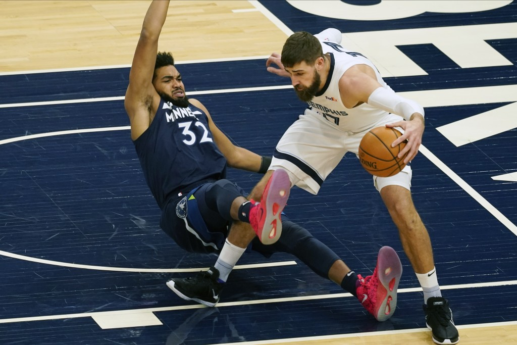 Minnesota Timberwolves' Karl-Anthony Towns, left, falls while getting tangled up with Memphis Grizzlies' Jonas Valanciunas in the first half of an NBA...
