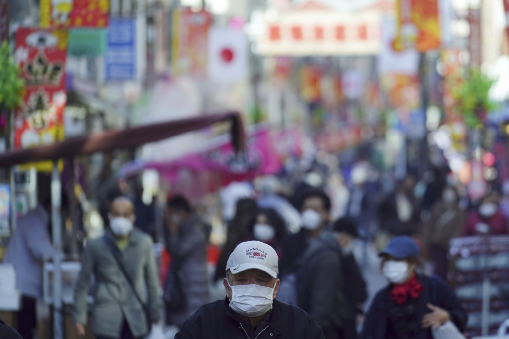 People wearing protective masks to help curb the spread of the coronavirus stroll along a shopping street in Tokyo Thursday, Jan. 14, 2021. The Japane...
