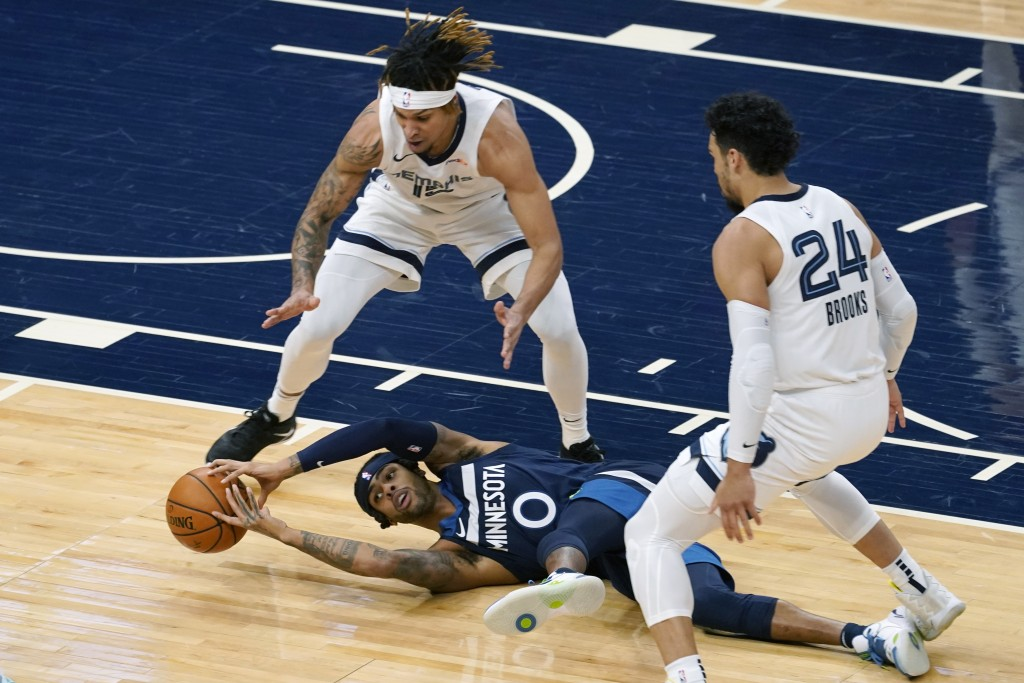 Minnesota Timberwolves' D'Angelo Russell (0) tries to grab the ball after falling while double-teamed by Memphis Grizzlies' Brandon Clarke and Dillon ...