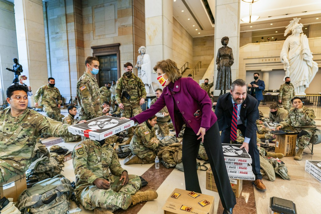 Rep. Vicky Hartzler, R-Mo., and Rep. Michael Waltz, R-Fla., hand pizzas to members of the National Guard gathered at the Capitol Visitor Center, Wedne...