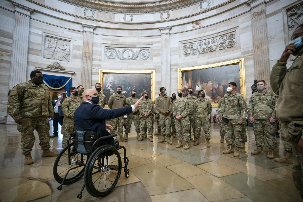 Rep. Brian Mast, R-Fla., left, visits with National Guard troops who are helping with security at the Capitol Rotunda in Washington, Wednesday, Jan. 1...