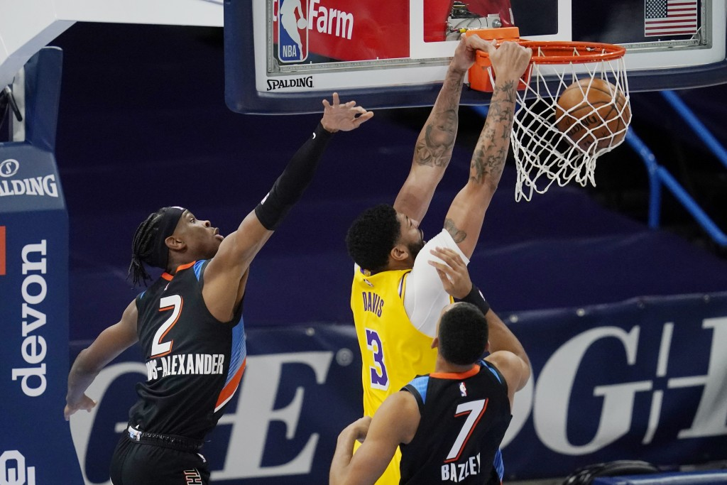 Los Angeles Lakers forward Anthony Davis (3) dunks in front of Oklahoma City Thunder guard Shai Gilgeous-Alexander (2) and forward Darius Bazley (7) d...