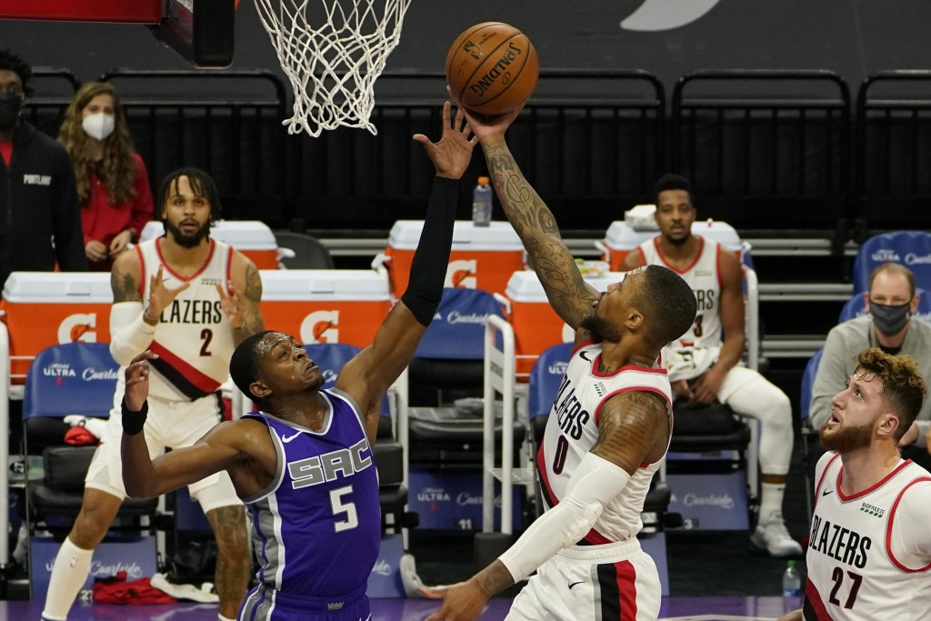 Portland Trail Blazers guard Damian Lillard, right, goes to the basket against Sacramento Kings guard De'Aaron Fox, left, during the first quarter of ...