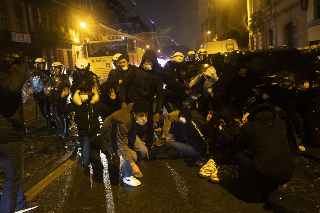 Protesters are blocked by police officers during clashes in the Belgium capital, Brussels, Wednesday, Jan. 13, 2021, at the end of a protest asking fo...