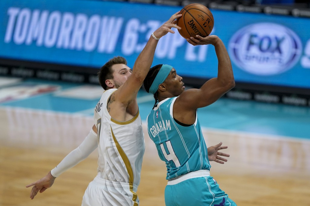 Dallas Mavericks guard Luka Doncic blocks a shot by Charlotte Hornets guard Devonte' Graham during the first half of an NBA basketball game in Charlot...