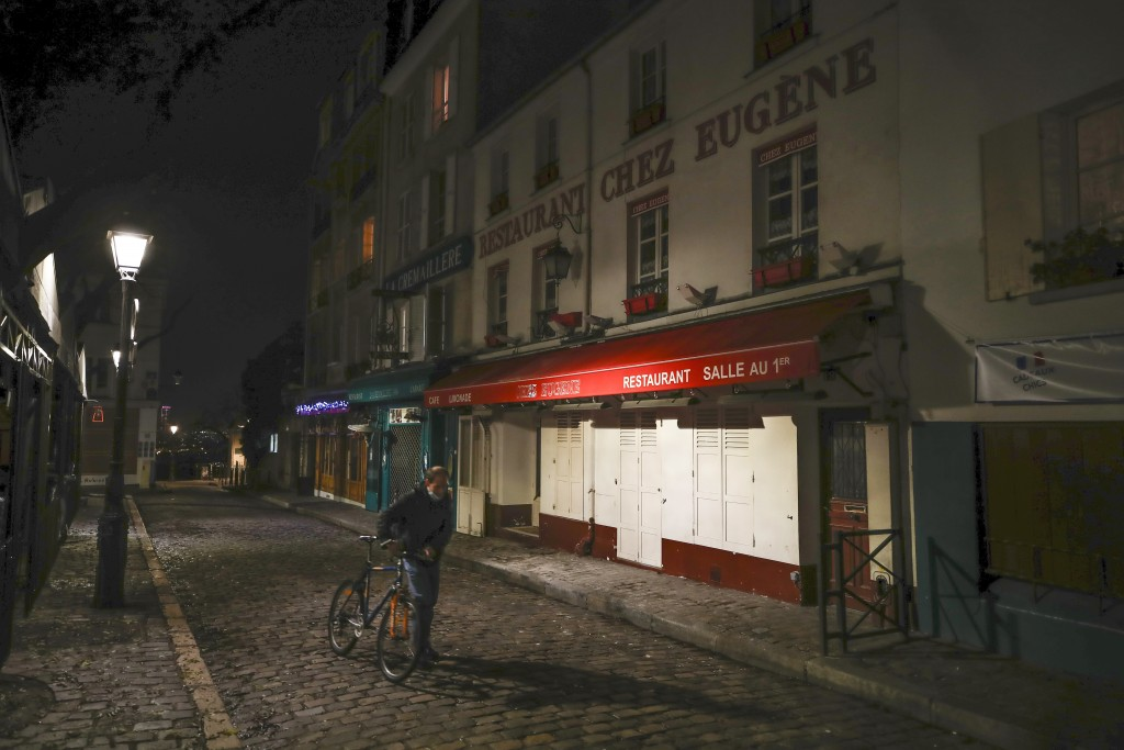 FILE - In this Dec. 15, 2020 file photo, a man pushes his bicycle along a row of closed restaurants in Montmartre, during the new imposed curfew in Pa...