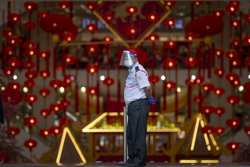 A security person wearing a face shield and face mask guards at the entrance of a shopping mall in Kuala Lumpur, Malaysia Thursday, Jan. 14, 2021. Mal...
