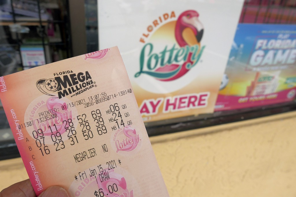 A customer shows off a Mega Millions lottery ticket after purchasing it, Wednesday, Jan. 13, 2021, in Orlando, Fla. Lottery players will have a shot F...