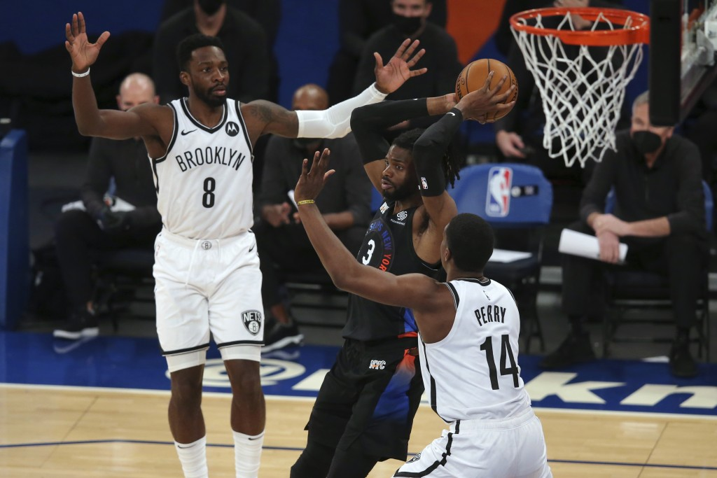 New York Knicks center Nerlens Noel (3) looks to pass the ball while defended by Brooklyn Nets forwards Jeff Green (8) and Reggie Perry (14) during th...