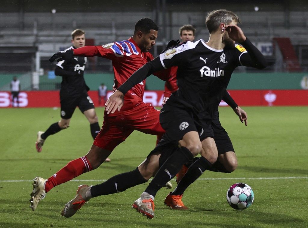 Kiel's Stefan Thesker, right, and Munich's Serge Gnabry in action during the DFB Cup 2nd round match between Holstein Kiel and Bayern Munich at the Ho...